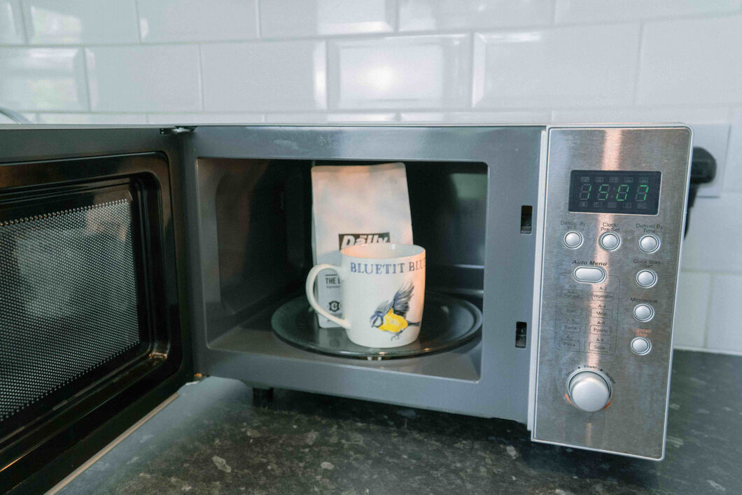 Bag of coffee beans and coffee mug in a microwave