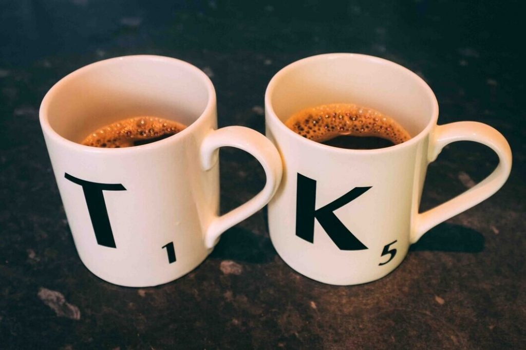 Scrabble K & T cups with black coffee in them.
