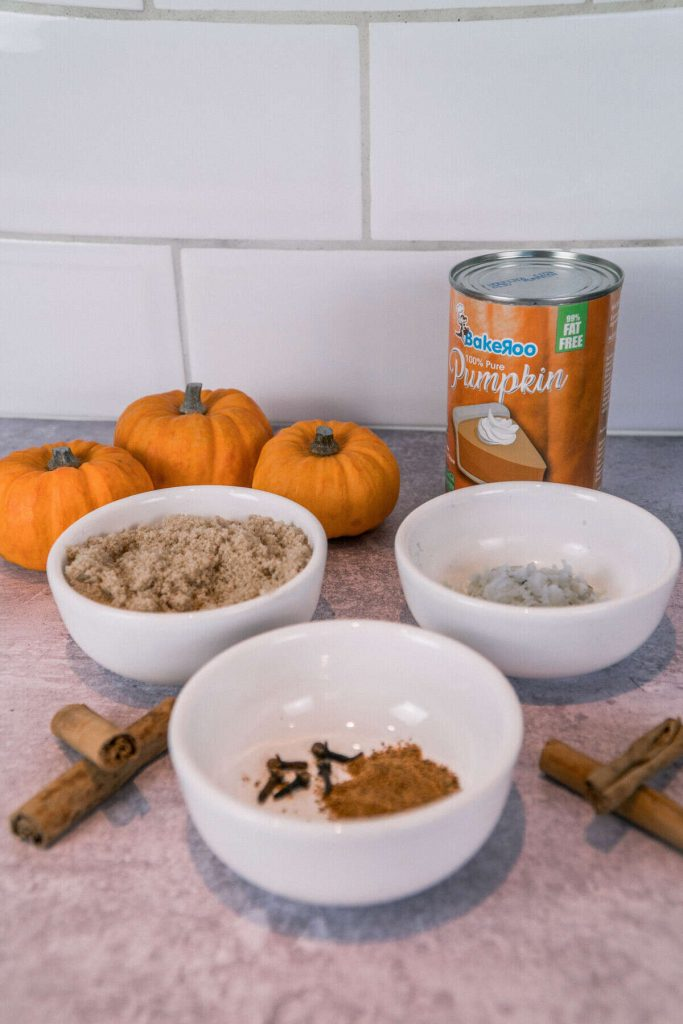 Ingredients to make the pumpkin spice syrup. Pumpkin puree, sugar, fresh ginger, whole cloves, cinnamon sticks and nutmeg.