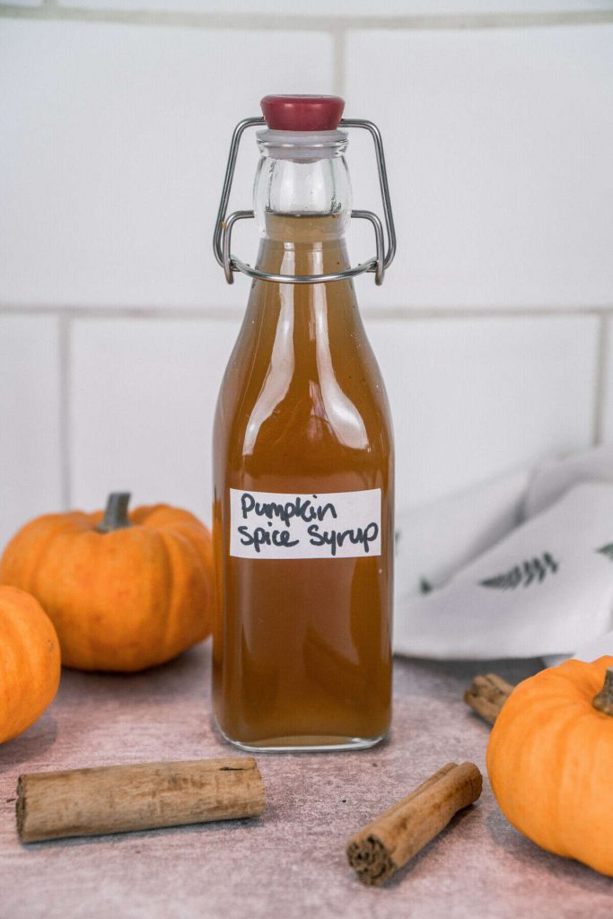 Pumpkin Spice Syrup with pumpkin, cinnamon sticks in the backgroud.