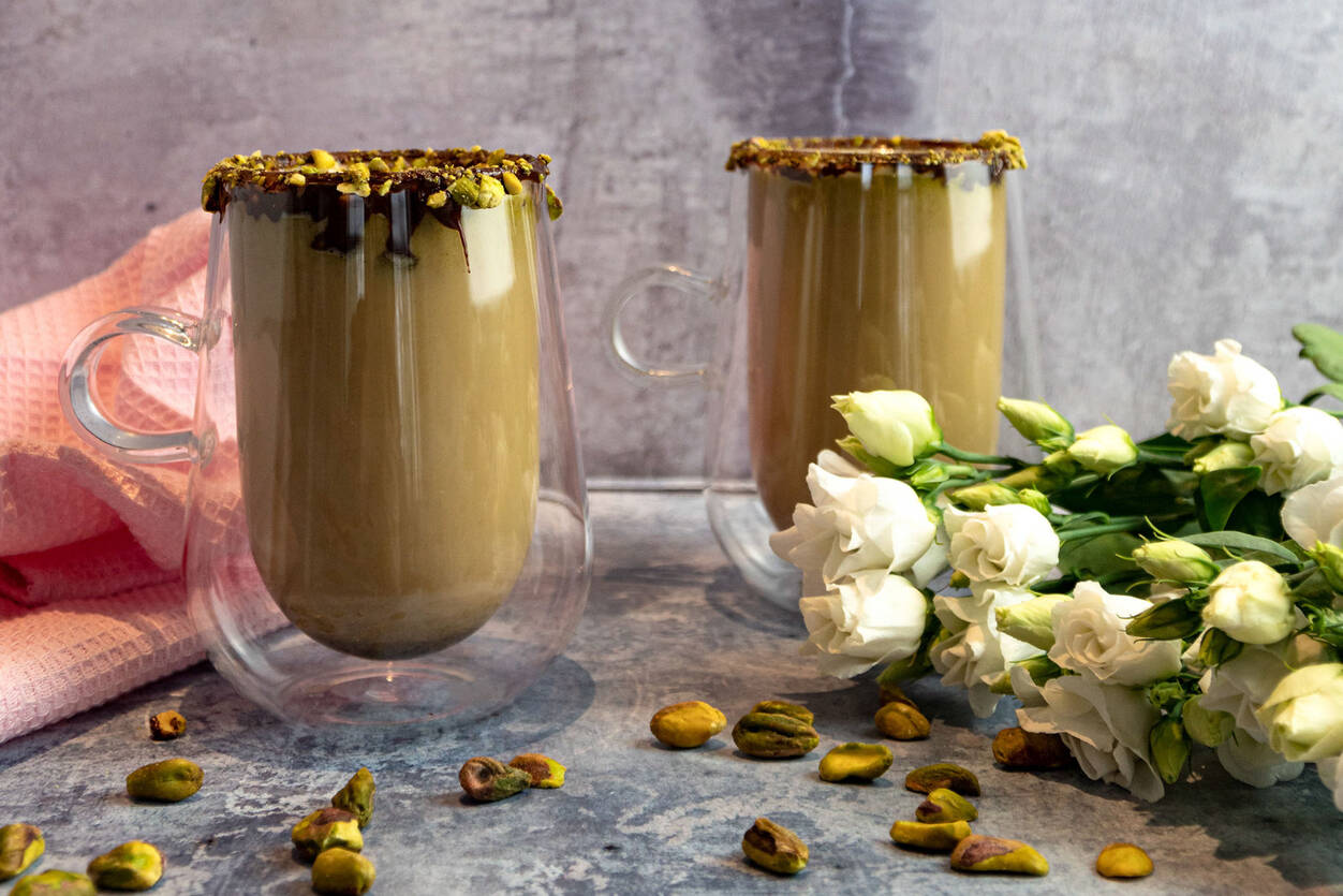 Pistachio Latte in a glass covered with chocolate and pistachio. Next to a pink tea towel, flowers and pistachios.