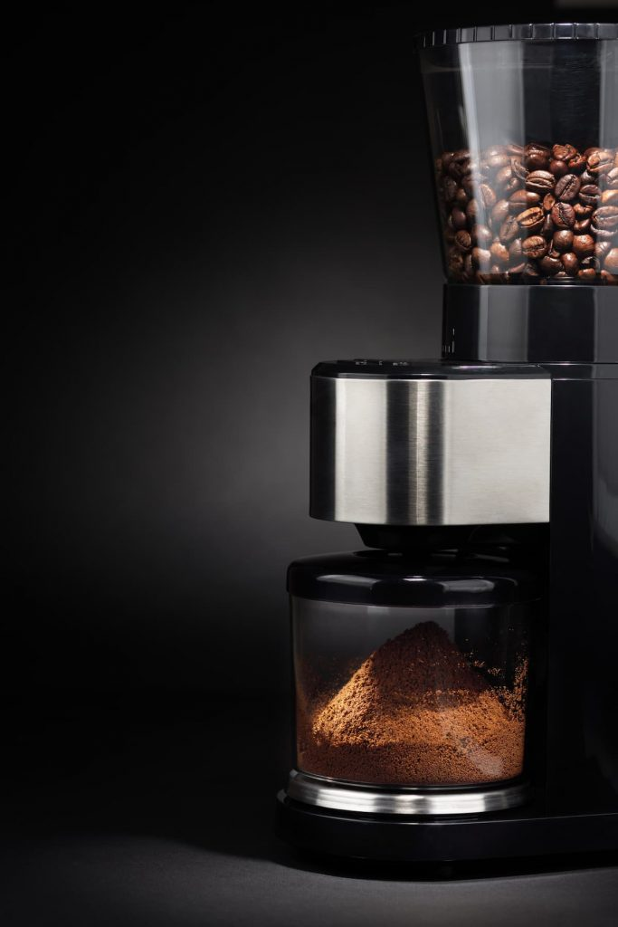Ground coffee pouring into a container from burr grinder