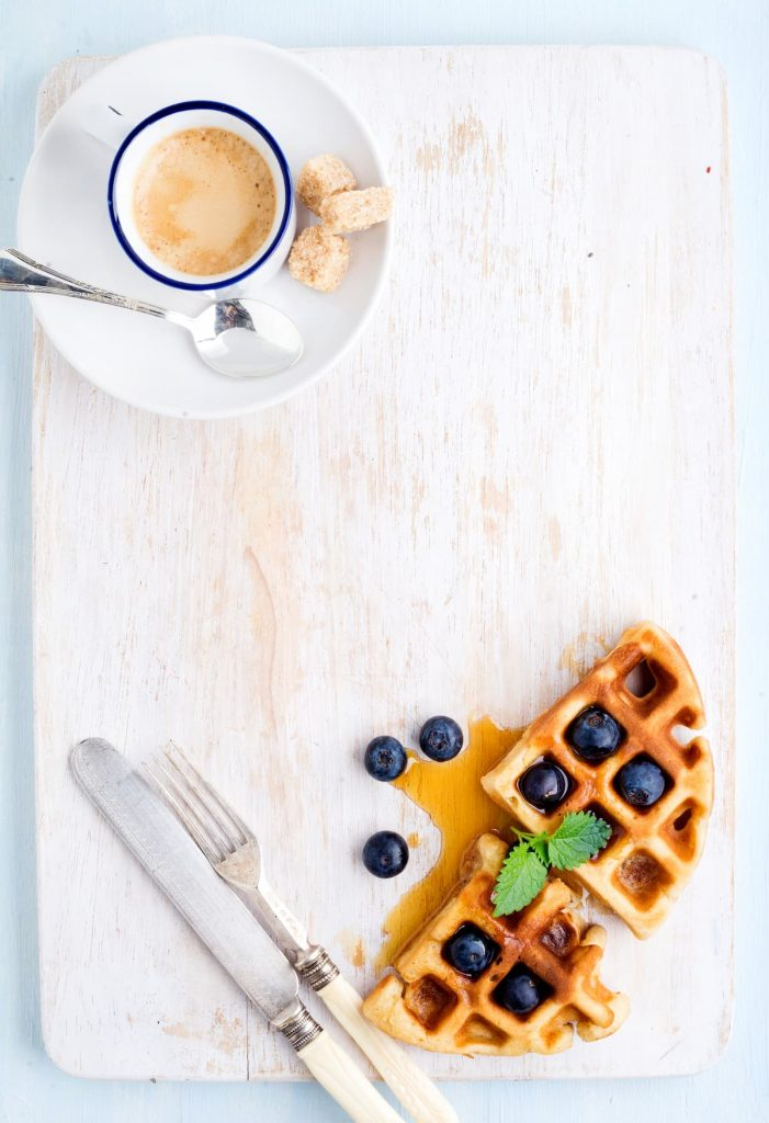 Espresso coffee cup, soft belgian waffles with fresh blueberries and marple syrup