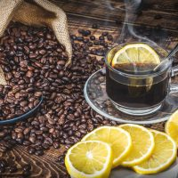 Espresso surrounded by lemon and coffee beans.