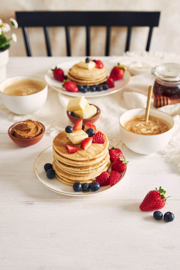 shot of pancakes with fruits on a plate near coffee and syrup at breakfast